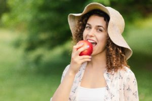 confident woman with dental implants biting into apple