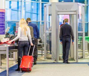 """Man walking into scanner, wondering, """"Will dental implants set off metal detectors?"""""""